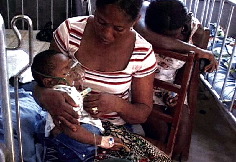 A woman cares for a baby on a respirator in a hospital in Ghana
