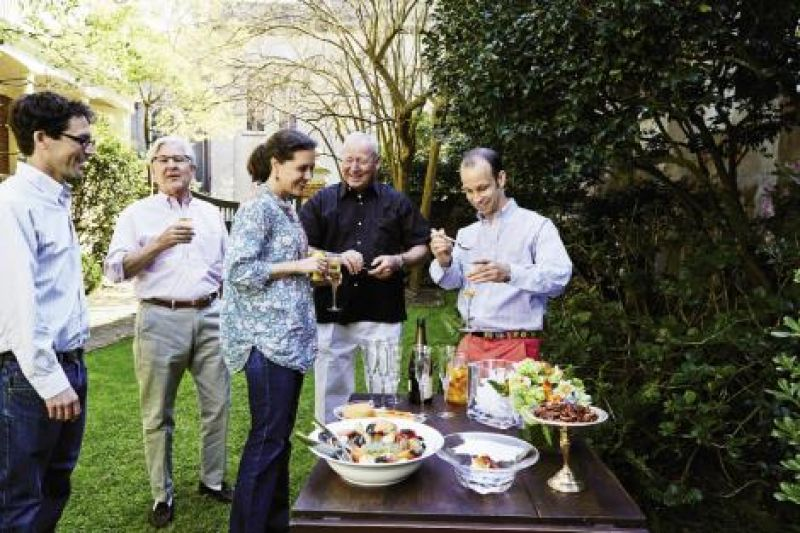 "Matt (right) mixes up some Kumquat Sparklers for (from left) Simons, Rutledge, and Sarah Moïse Young and her dad, Ben. Snacks that await on the table include the highly addictive ""Henry's Cheese Spread,"" which was served alongside crudité on every table of the famed Charleston restaurant Henry's; stone crab claws from the Stono River with ""Ashley Avenue Bay Butter;"" and spiced pecans from a fall Chalmers Street harvest. (inset) Hosts Kathleen and Rutledge Young."