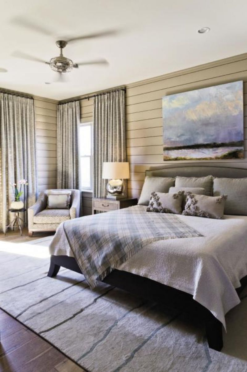 Mellow Out: Poplar wood paneling wraps a master bedroom (one of two in the house). The Tufenkian rug is from Tibet and the landscape painting is from Rebekah Jacob Gallery.