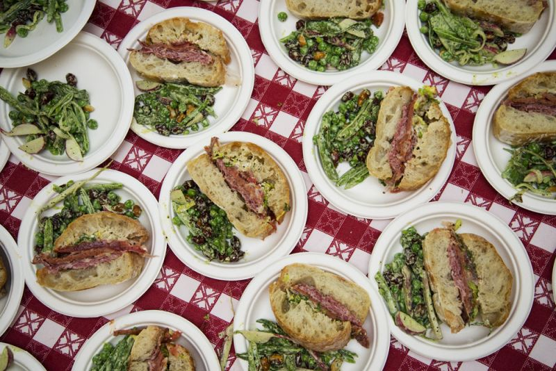 Sandwiches piled with salami cotta from Keegan-Filion, provolone, lettuce, tomato, AMS sauce, and focaccia are paired with an English pea salad featuring peanuts, green garlic, buttermilk dressing, peas from Rosebank Farms, and radishes from Rebellion Farms.