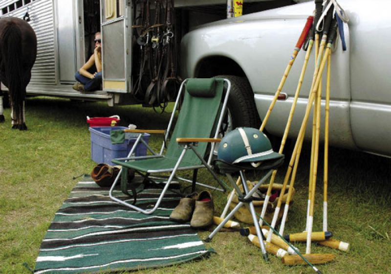 Bridles are hung on the trailer, and each player sets up a spot to kick off his shoes and pull on his boots.