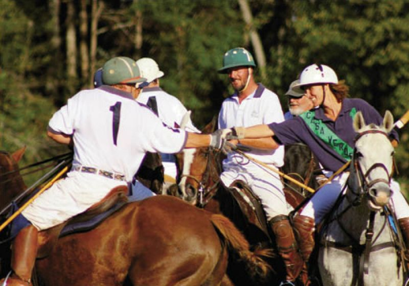 After the shouldering ferocity of the chukkers and the windup for a final shot, all eight players meet on the field to shake hands at the end of the match. Three players leaning in for this bit of polo etiquette are Barry Limehouse, Todd Martineau, and Elisa Cashin.