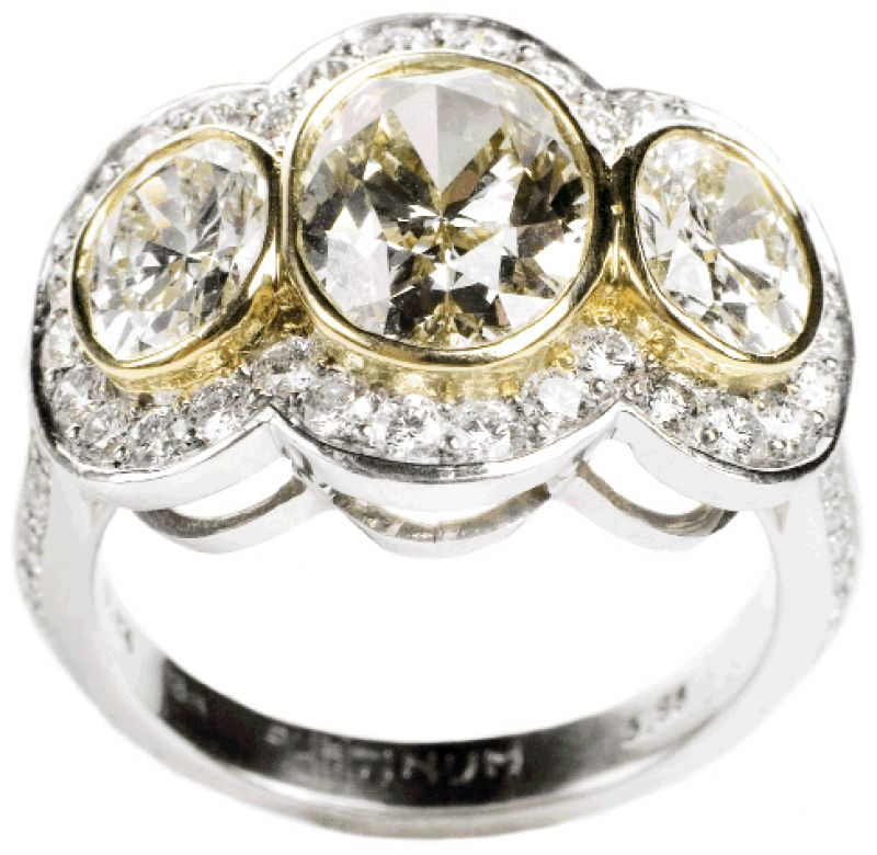 THREE TIMES THE CHARM:  Platinum ring with 18K yellow gold, 2.51 ct.  center diamond, and two yellow diamonds with accent diamonds (2.31 total ct.) Skatell's, $35,750