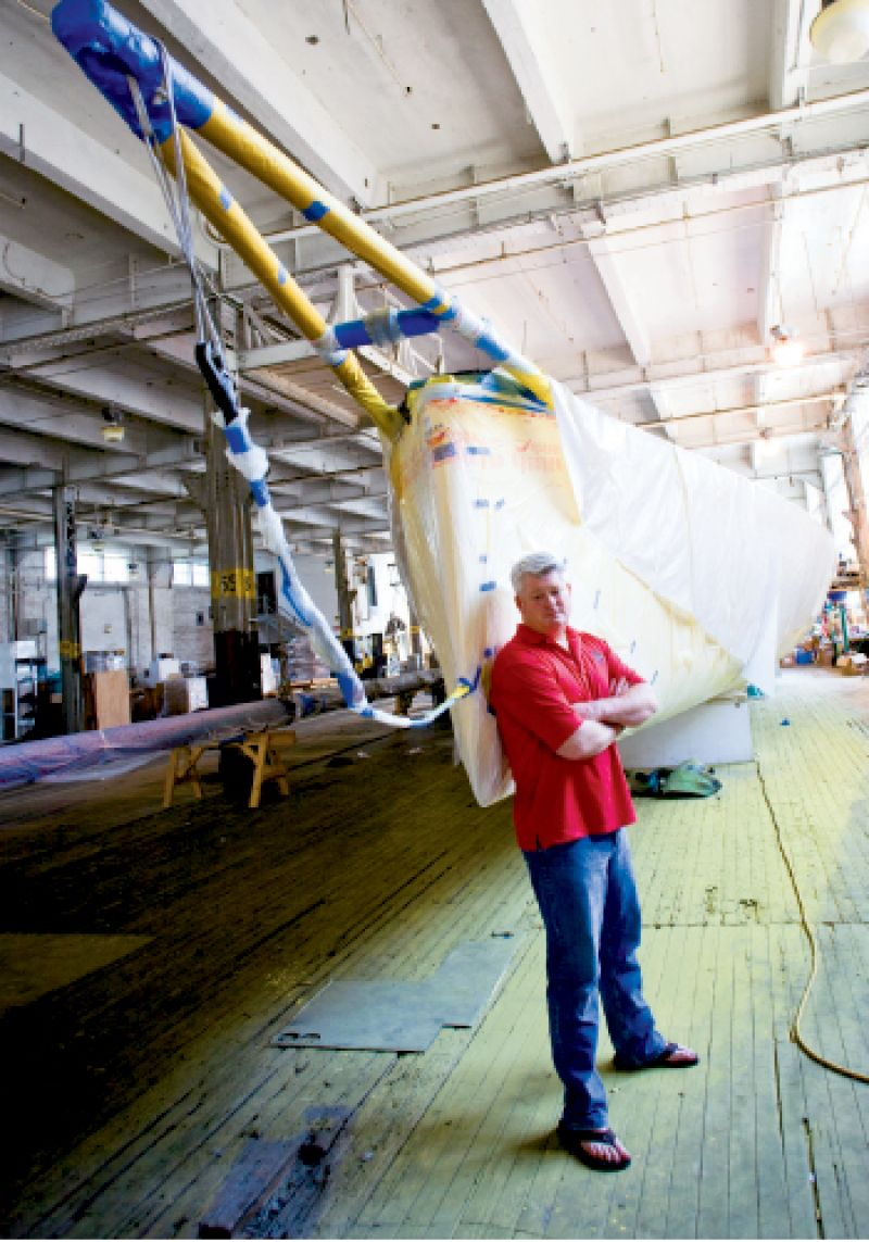In a North Charleston warehouse, the boat is stripped, sanded, and painted. The crew will also outfit the vessel with new hardware, electronics, wiring, and sails. Photograph by Kaitlyn Iserman.