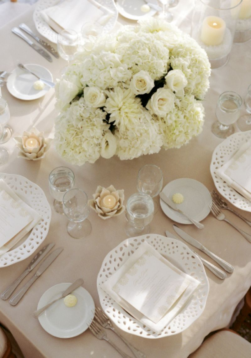 ZONE OF NEUTRALITY: Cream-colored hydrangeas and roses plus delicate white dinnerware and sculptural votive holders offset a khaki backdrop that, on its own, could have washed out the reception space.