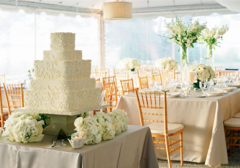 "CHAMPAGNE DREAMS: ""We used khaki and white stripes on the tablecloths to give everything a little bit of a preppy twist,"" says Jane of the dining area, where Jim Smeal's ivory wedding cake became part of the décor."