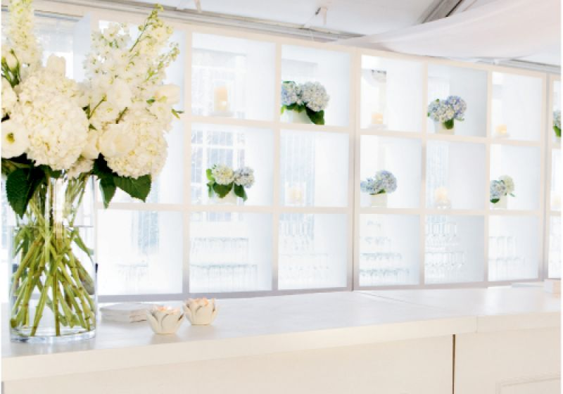 SOMETHING BLUE: Heather Barrie of gathering—floral + event design tucked low vases of pale blue hydrangeas in a shelf in the bar area for a soft, secondary accent color.