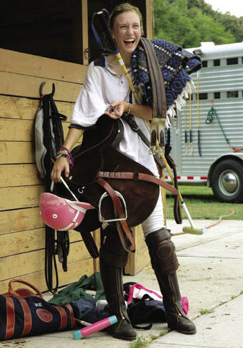 Eliza Limehouse, 14 years old and a fan of the color pink, carries her tack for a spring scrimmage game. She wears leather kneepads for protection and over-chaps to save her boots from wear. She's a dedicated player, as evidenced by the tiny polo horse illustration on her retainer.