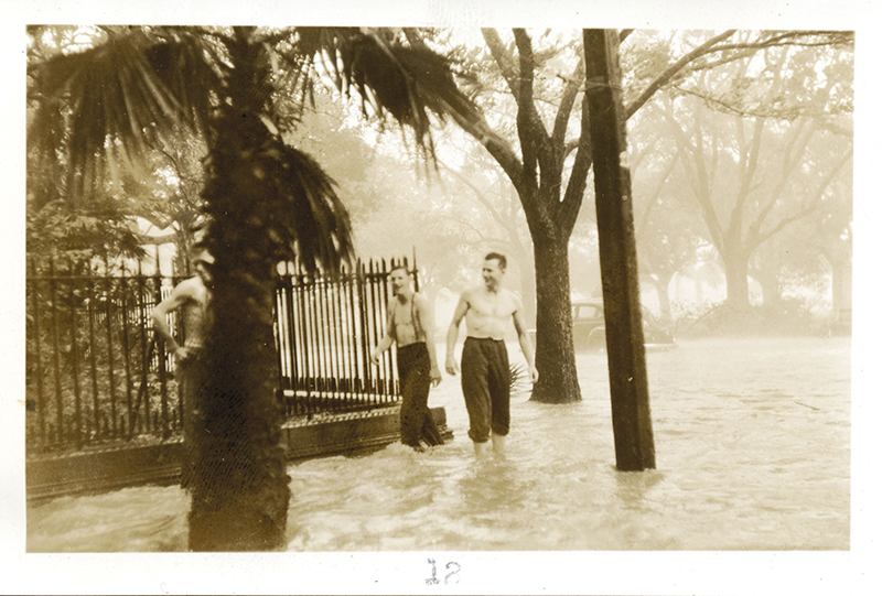 Two men wade at the corner of Meeting and South Battery, and cars are flooded at the end of King Street and South Battery.  Photograph courtesy of The Charleston Museum