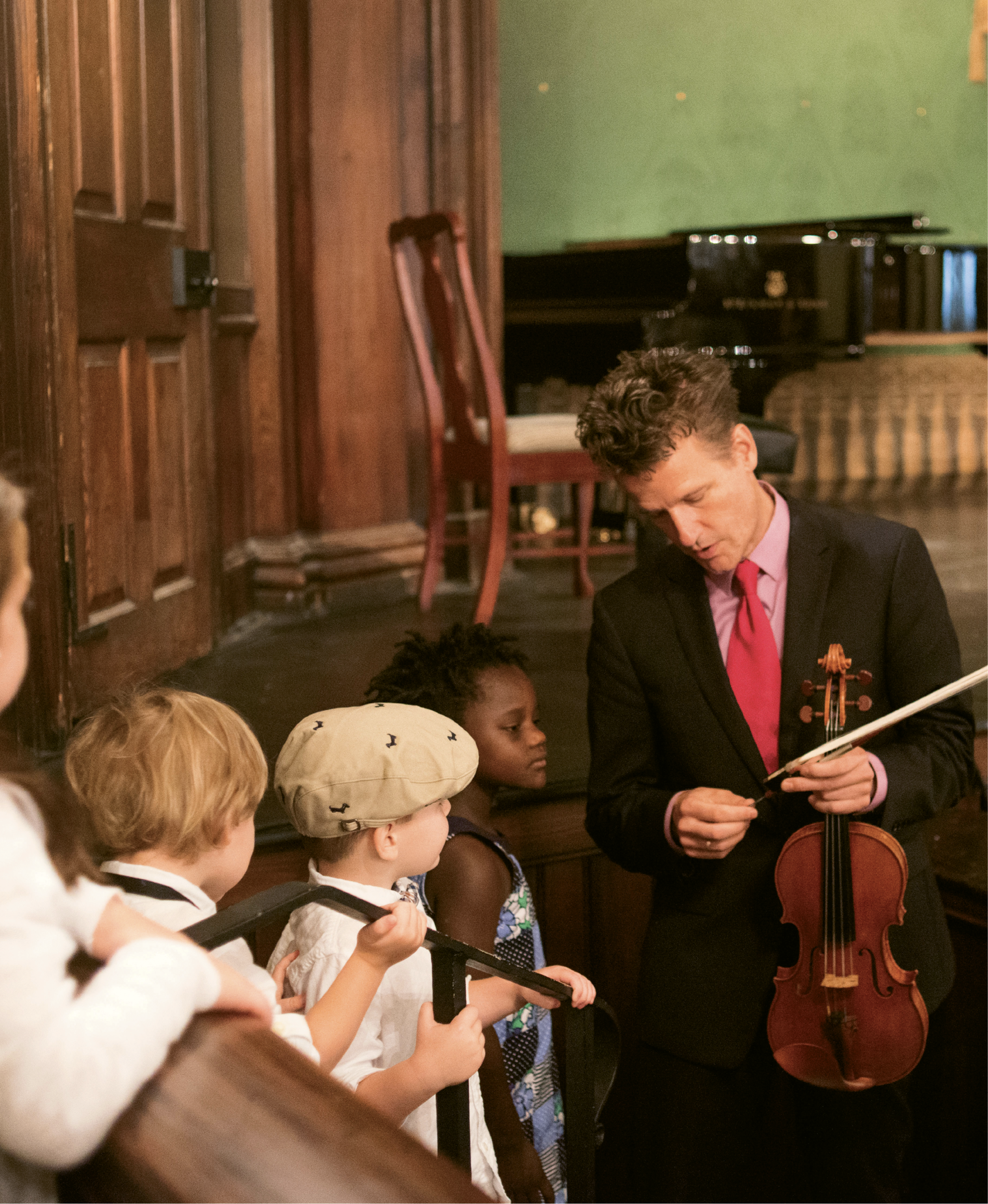 Child's Play: Every festival season, Nuttall spends about six hours with local kids for outreach programs. Here, some children get a close look at Nuttall's violin and bow after a special concert for individuals with autism and their families.
