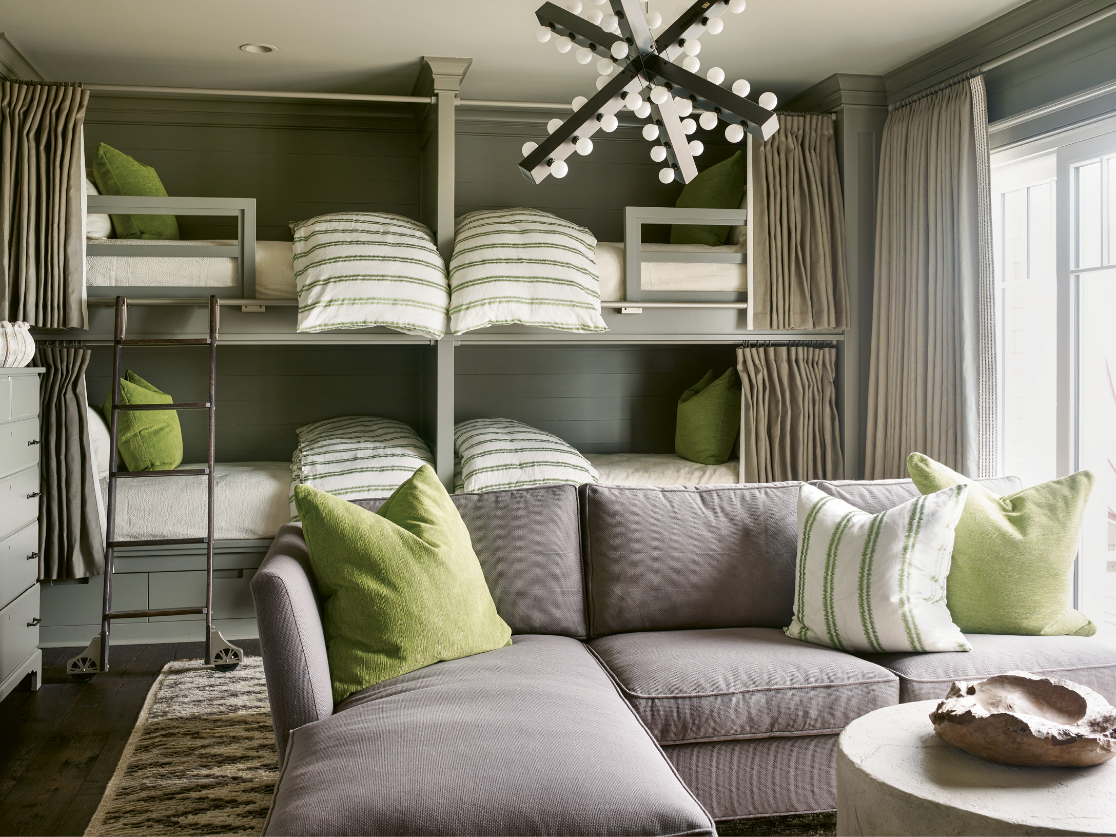 The bunk room's cool comforts include the slate grey walls, shag Moroccan carpet, and pops of lime green.