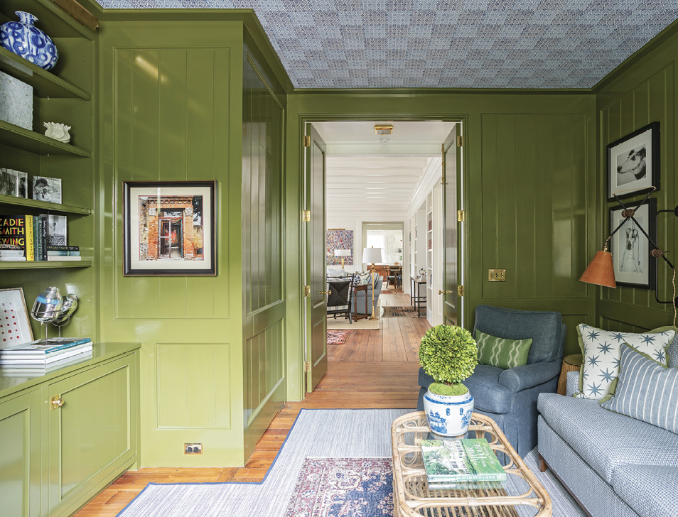 """Lacquered in Farrow & Ball's bold green """"Bancha,"""" the adjoining media room is a cozy place to watch a movie or curl up with a good book. Peter Fasano wallpaper on the ceiling gives the feel of mosaic tile."""