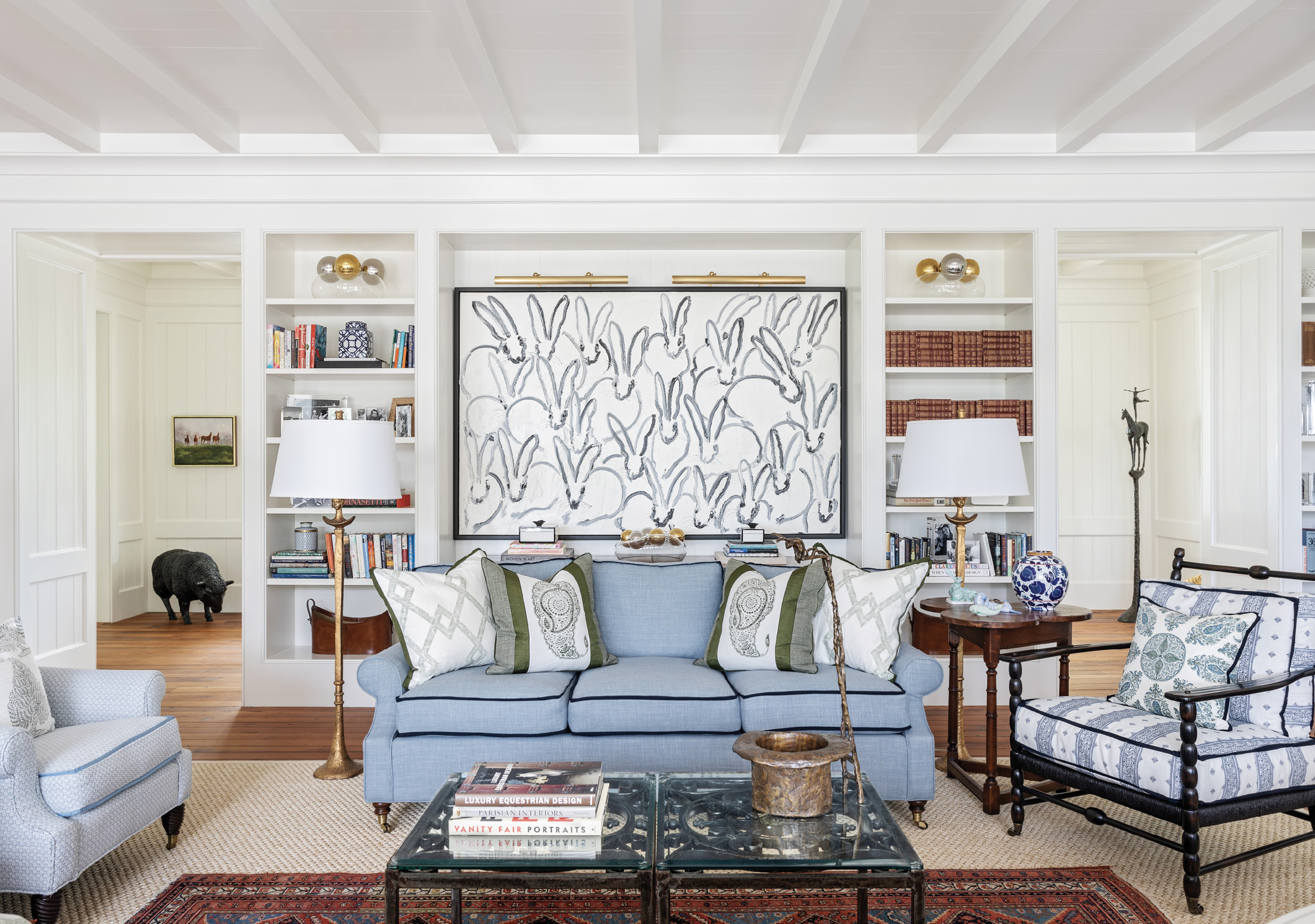 """The architects designed spaces for the client's artwork, such as this built-in made for Hunt Slonem's Bunnies. Interior designer Melissa Ervin designed the living room to be comfortable and livable with a green and blue color palette playing on the natural scene beyond its large windows. The Edward Ferrell sofa is covered in CalvinFabric's """"Camino-Lake,"""" tipped with grosgrain ribbon, a small detail with a large impact."""