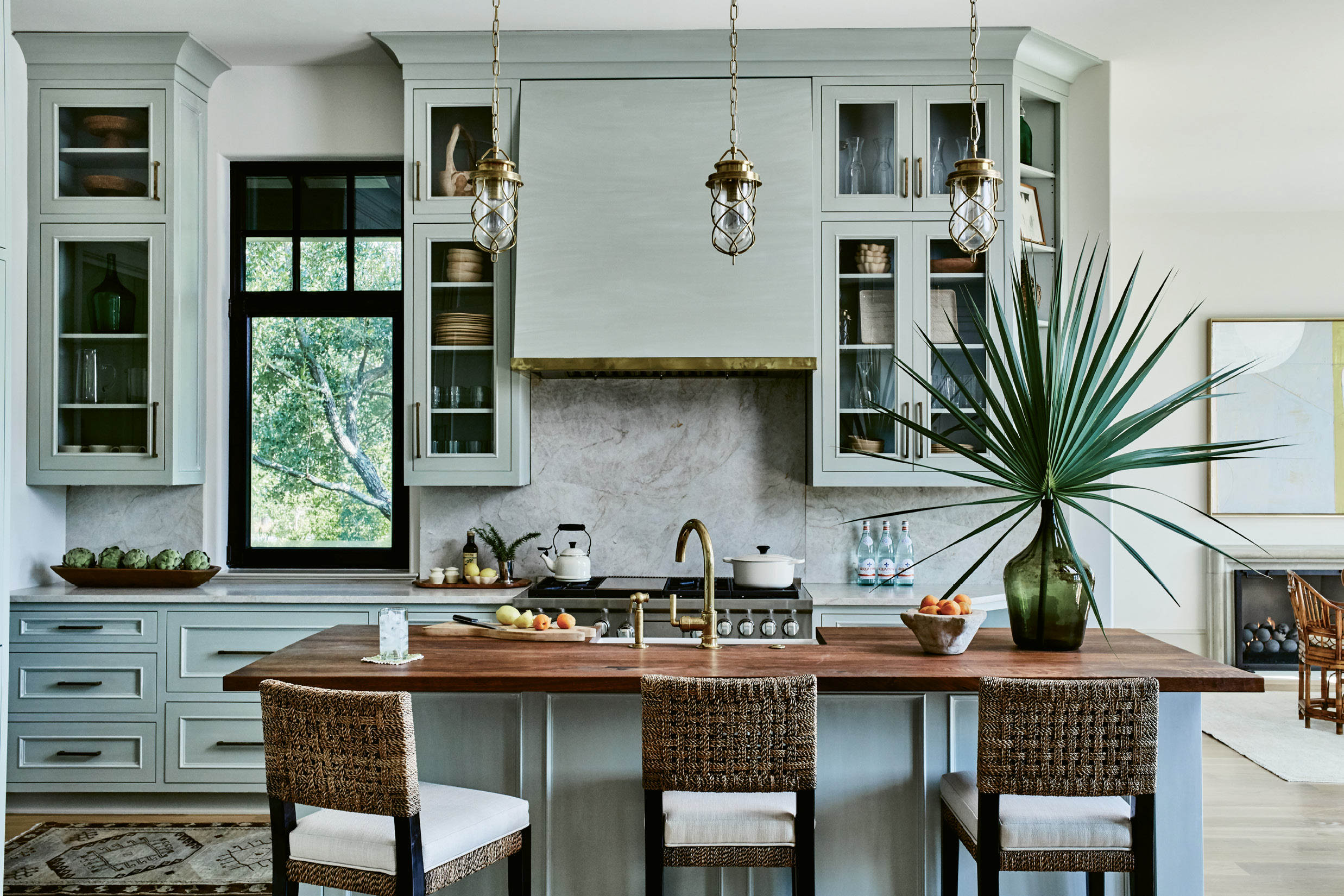 "WARM & INVITING: Brass accents—the faucet, pendant lighting, and custom trim around the hood—continue in the kitchen. ""It complements the soft sage-green cabinetry and warms up the space,"" says interior designer Charlotte Lucas. She chose quartzite for the countertops and backsplash for its hue and durability and walnut to top the island for additional warmth and interest."