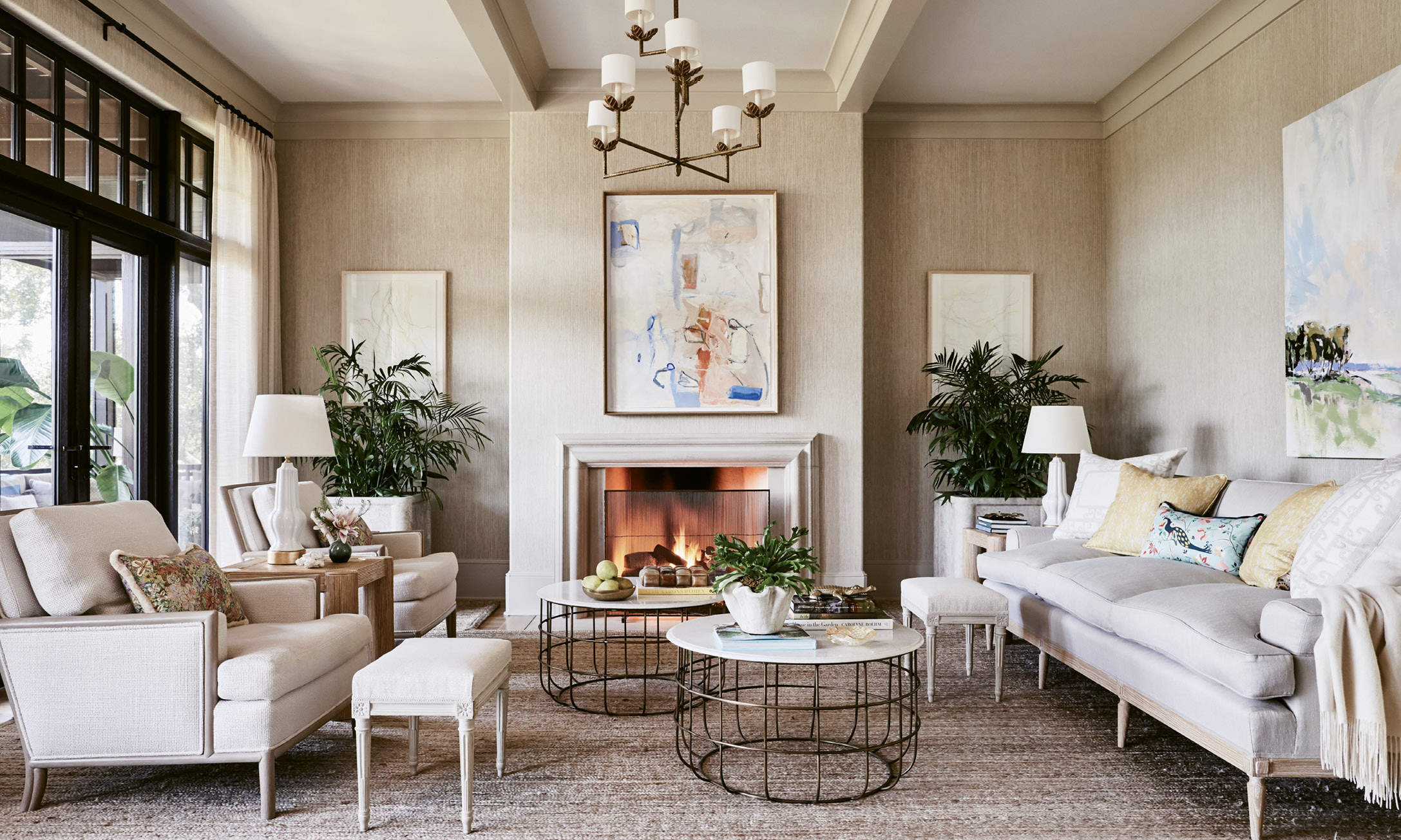 Neutral Territory: In the living room, a neutral yet textured sandy palette, including grasscloth-covered walls and upholstered linen sofa and chairs, allows the expansive marsh view to take center stage. The Frank Phillips painting over the mantel, found at George Gallery, as well as some commissioned works, provide splashes of subtle color. Bamboo and brass accents add dimension.