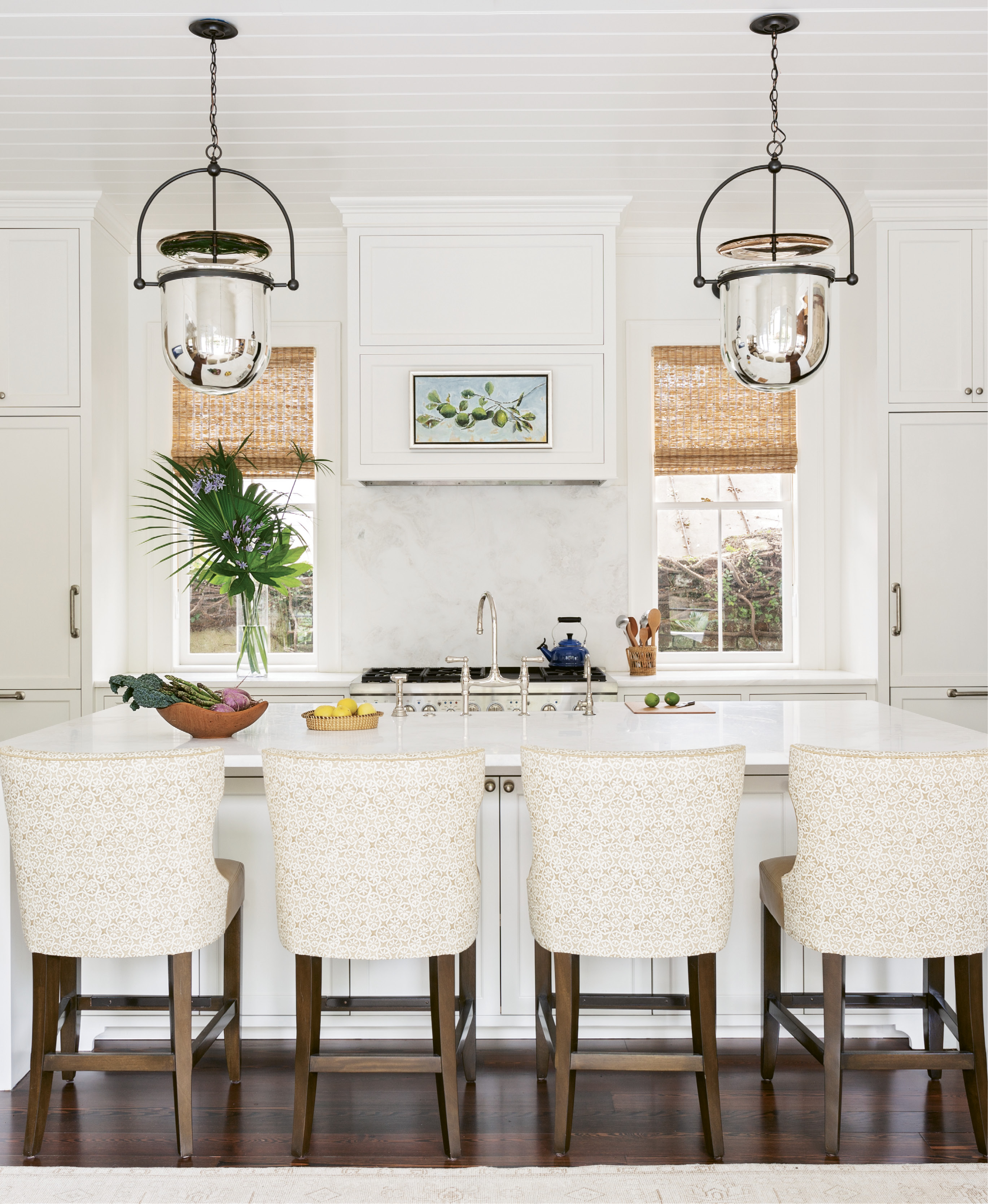 "SIMPLE SYMMETRY: Dominated by a large white Namib marble-topped island, ideal for gathering the family as well as spreading out the newspaper, the kitchen is literally and figuratively the heart of this home. A pair of ""Urban Smokebell"" lanterns from Urban Electric add a grand scale and align perfectly with the two newly discovered windows, previously covered by cabinets."
