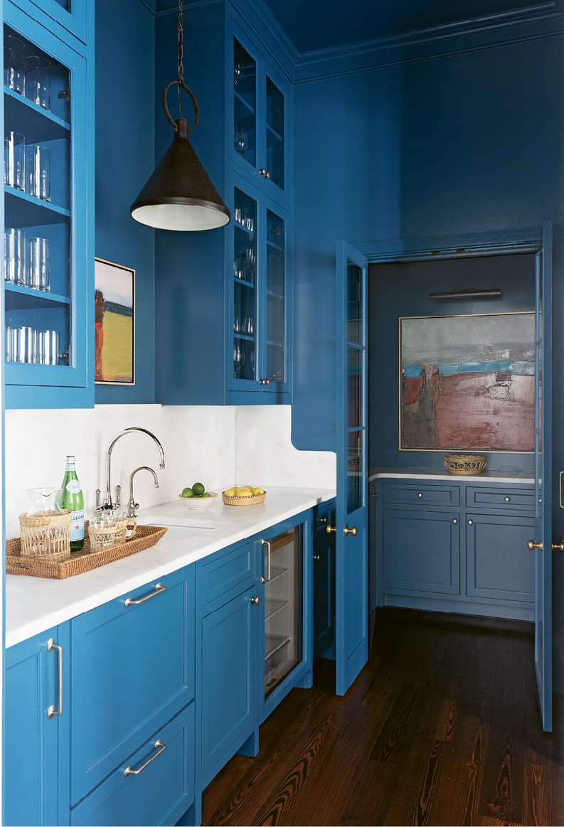 "BRIGHT SPOT: Cabinets lacquered in Benjamin Moore ""Blue Danube"" pull the eye through the neutral kitchen into this daring butler's pantry. Two Sandy Ostrau works from Meyer Vogl Gallery add to the dramatic, contemporary feel."