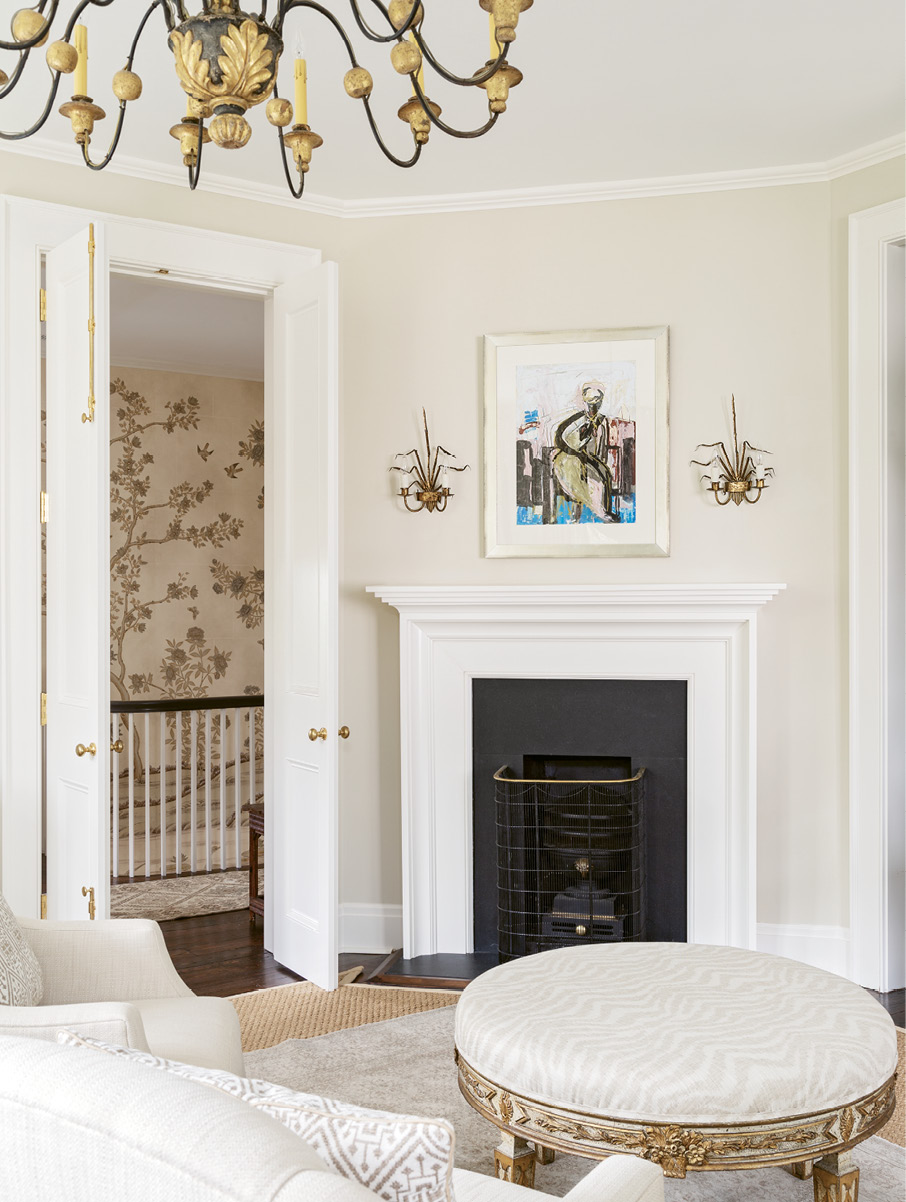 A pair of early-20th-century Spanish Barcelona gilt tole sconces from David Skinner Antiques flank an Anne Darby Parker oil above the fireplace.