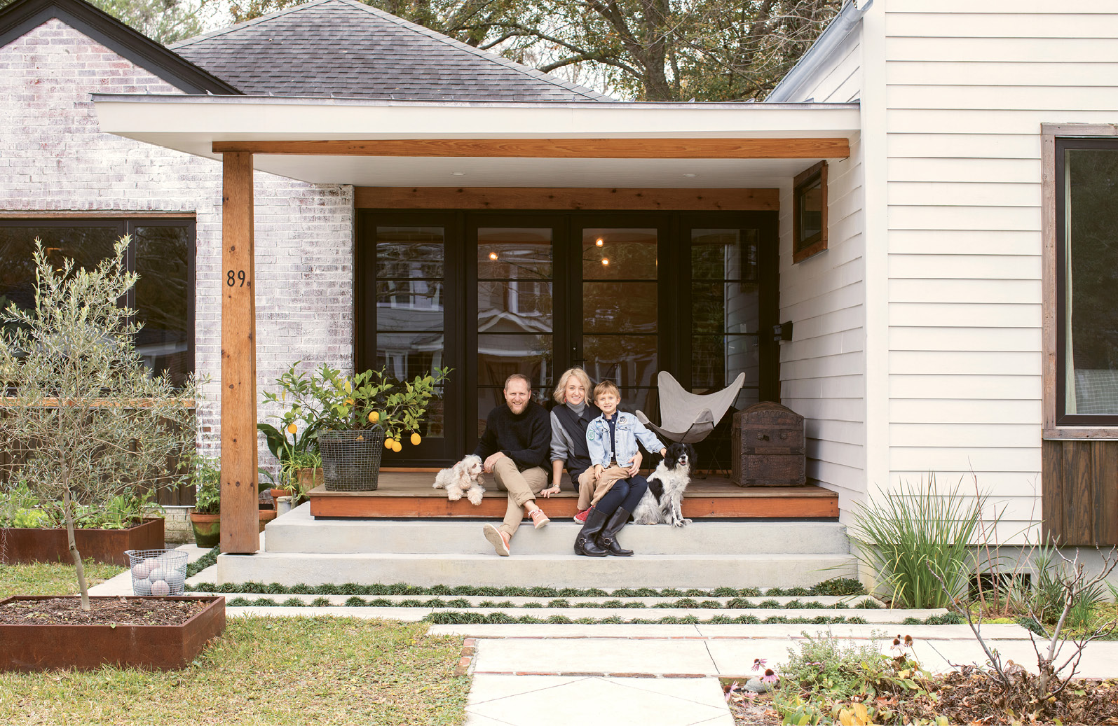 Jacques and Carrie Larson, pictured here with six-year-old son Jack and pups Lily Bean and Maggie Mayhem, hired Alicia Reed of Reggie Gibson Architects to help them transform their West Ashley cottage into a modern home perfect for the way their family lives and eats. Much of the landscape is devoted to edible plants, including an olive tree
