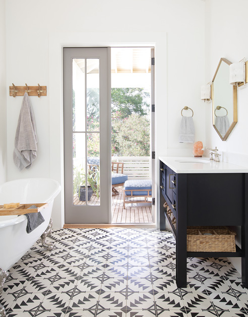 "The adjoining bath features the same tile as the kitchen backsplash, custom vanities by cabinetmaker David Beason, a clawfoot tub from Moluf's, and two ""Drake"" hemp-wrapped brass wall sconces from Ro Sham Beaux. Both rooms open to a private porch outfitted with cushioned teak chaise lounges and chairs from Tommy Bahama."