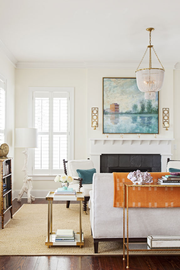 In the living room, a woven rug, creamy white walls, and neutral upholstered pieces contrast nicely with an orange throw, a violet velvet chair, and a blue-hued Linda Fantuzzo painting depicting I'On a decade ago.