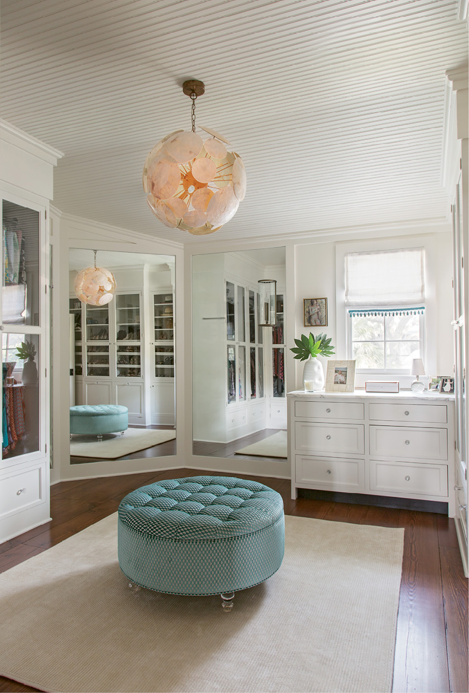 DRESSED FOR SUCCESS: In the dressing room, an Oly light fixture and tufted blue ottoman set an elegant tone.