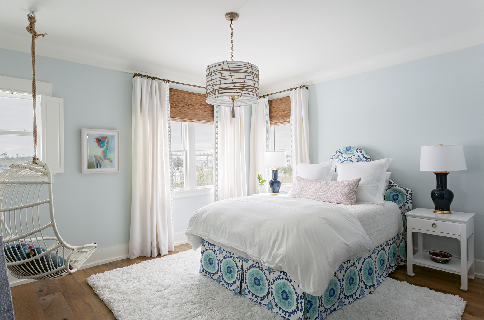 "The McElveens' youngest daughter's bedroom boasts eye-catching fabrics, from the custom-made bench in the Galbraith & Paul ""Seville Tile"" print in the master to the linen headboard with matching blue Quadrille bed skirt."