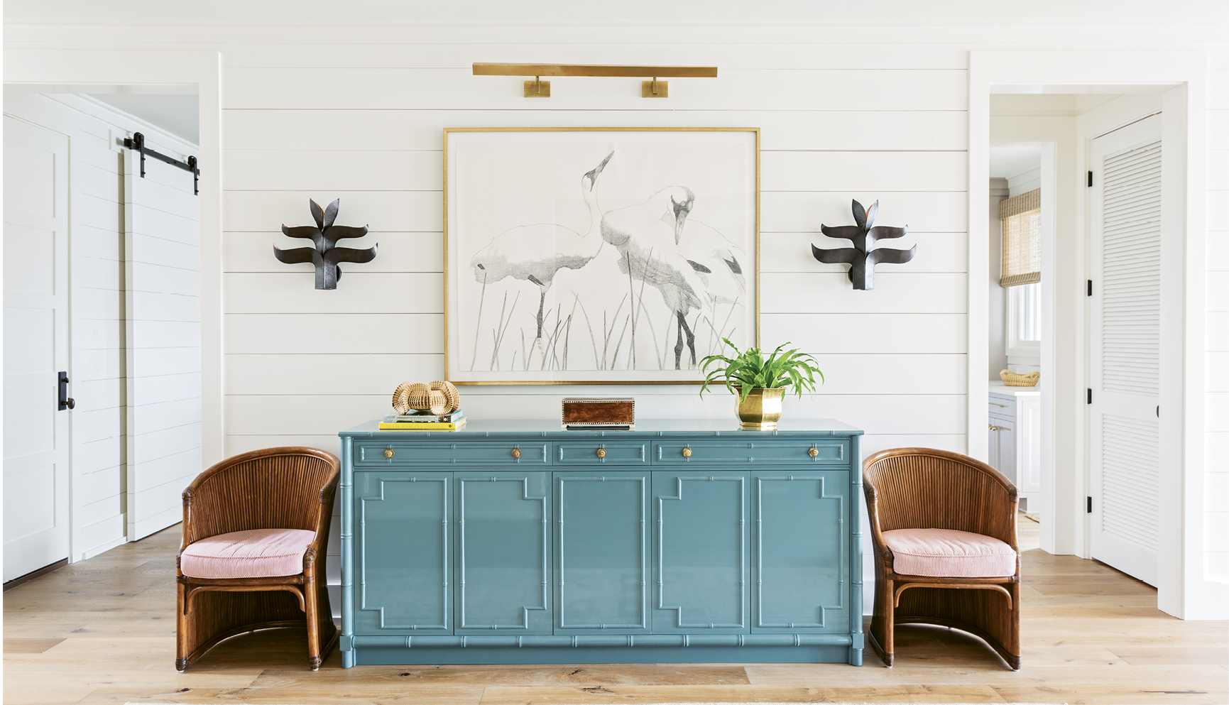 "Perky Pastels: A custom-designed French blue credenza punctuates the McElveens' expansive entryway. Two vintage chairs from Charleston's Indigo Market and a Judith Vivell charcoal drawing, ""Whopping Cranes in Reeds II,"" finish off the vignette."