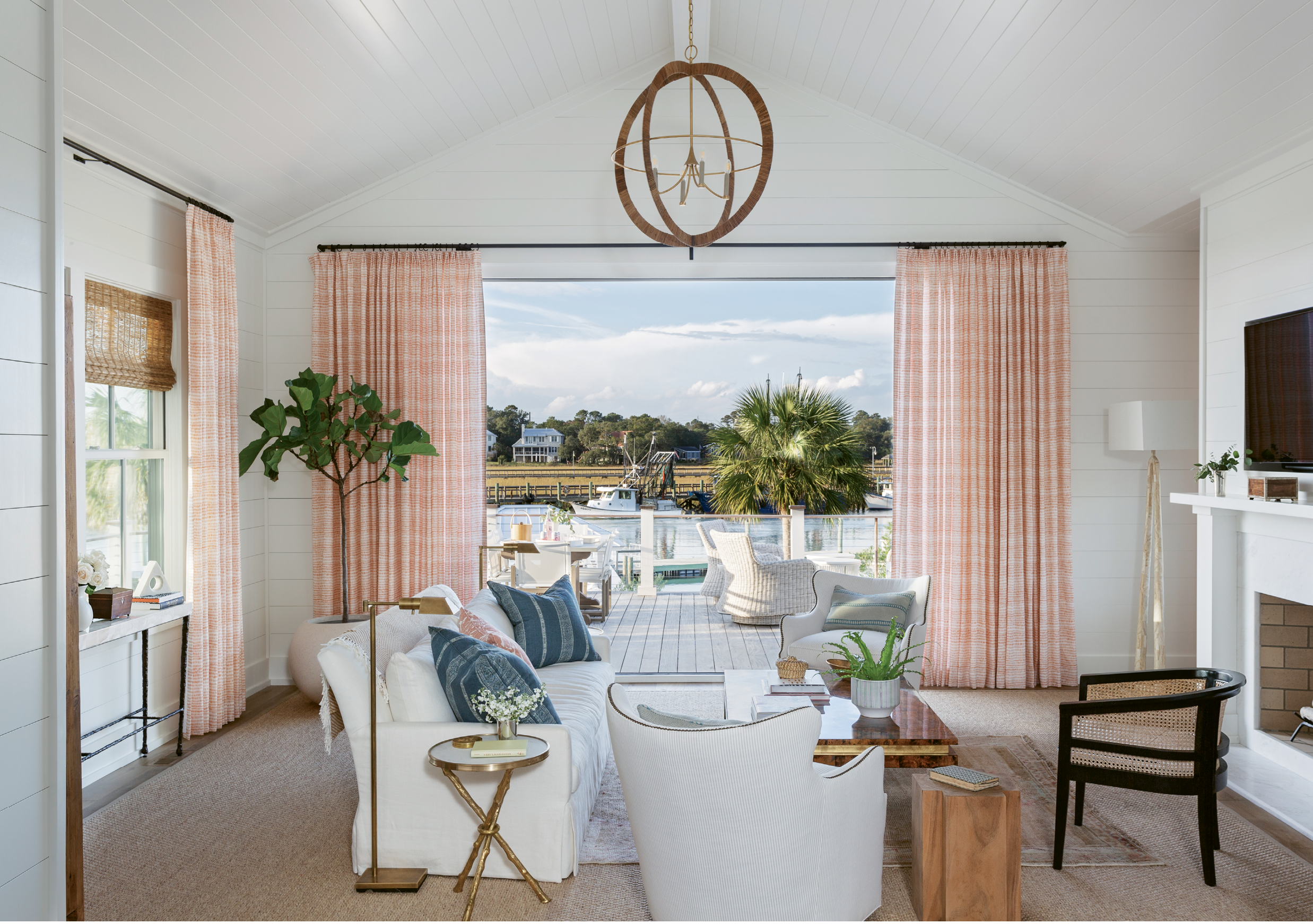 Calming hues repeat in the main sitting room, where tangerine linen curtains in a Rebecca Atwood print flutter through the breeze wafting in from Shem Creek.