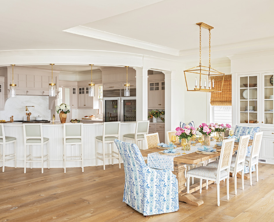 """GATHER ROUND: The curved, two-tier kitchen island, original to the home, is a high-traffic area, for the boys especially. """"I like to see them all lined up there just like when they were little,"""" says Amy, noting they had a similar island decades ago. Formerly a mix of white and dark wood, the kitchen cabinets now wear Farrow & Ball's """"Elephant's Breath,"""" with a hint of pink. """"It's so beautiful when you get that sunset light coming in,"""" says Allison. Glass and brass pendants from Circa Lighting add further warmth to the space."""