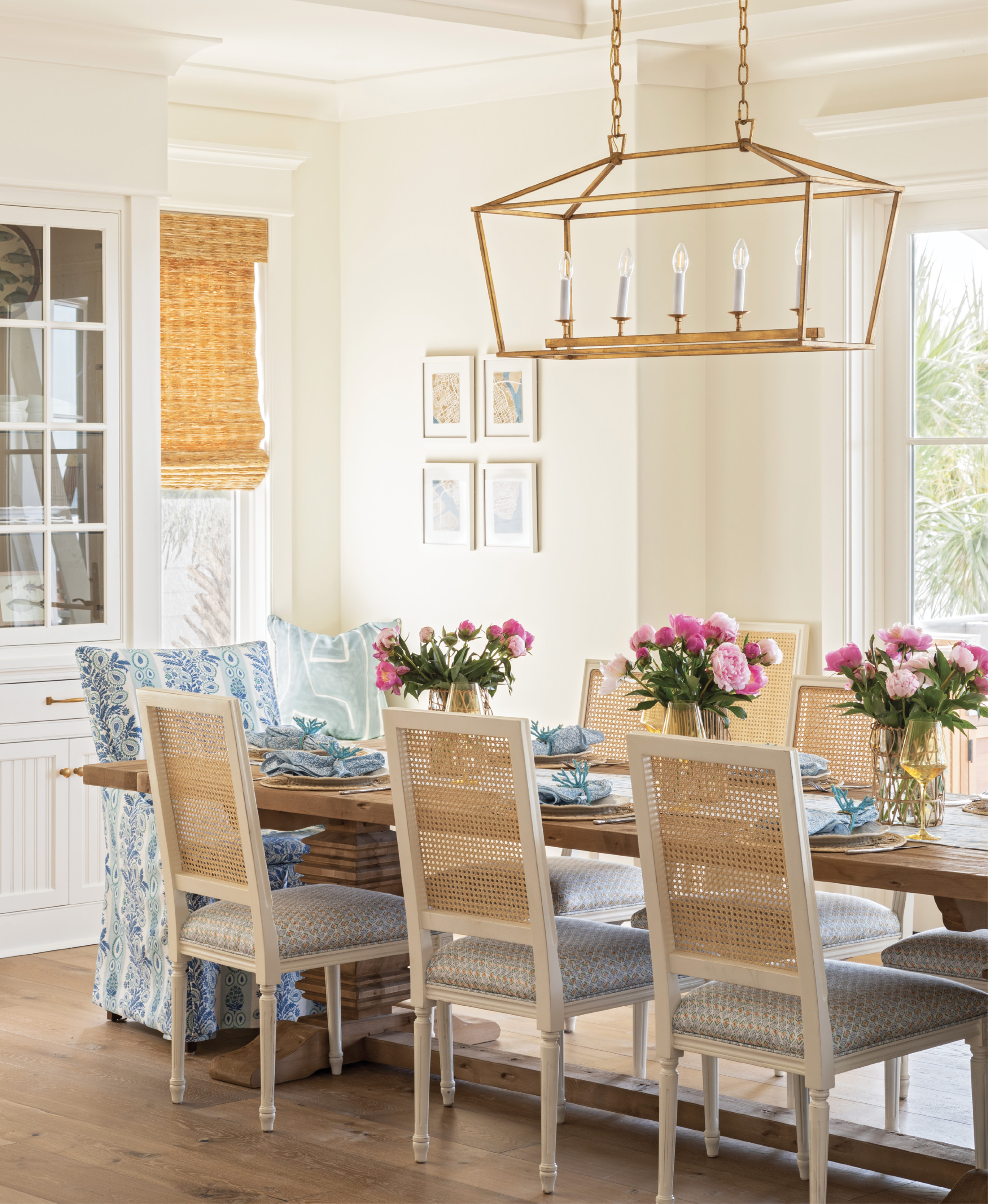 GOOD VIBES: In the dining area, windows were replaced with French doors, flooding the space with natural light and making a more direct thoroughfare to the outdoor kitchen. A fun suite of fabrics—by Rebecca Atwood (cane-back chair seats), Charlotte Gaisford (slipcovered host chairs), and Kelly Wearstler (window seat pillow)—energize the space, which centers around a sweeping Restoration Hardware trestle table.