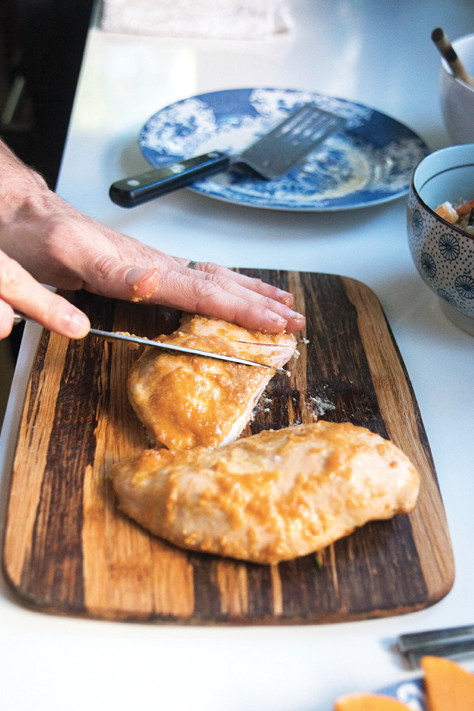 To serve the miso chicken, slice the cooked breasts on the diagonal. Walker plates his with an arrangement of seasonal fruit.