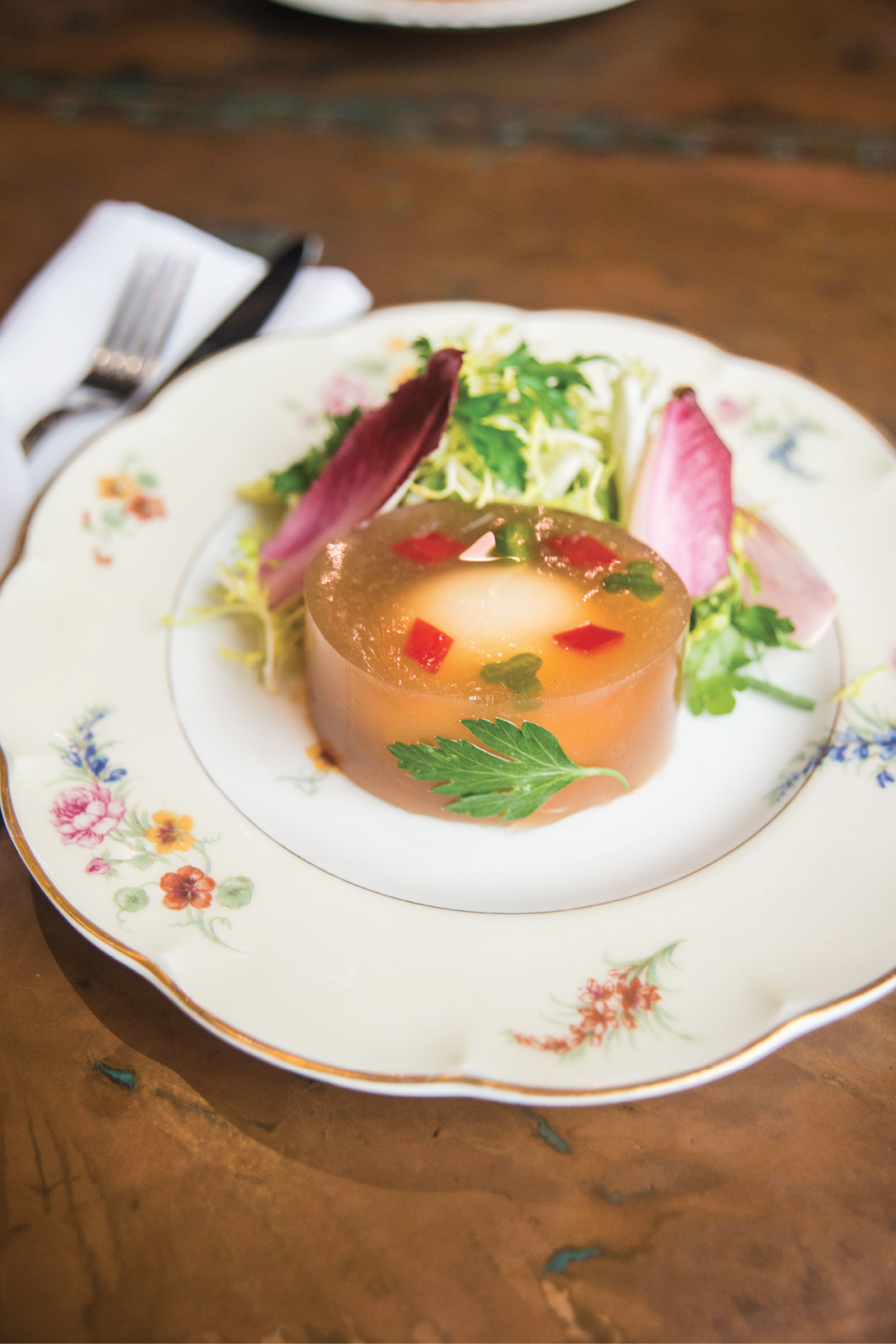 Suspended Animation: A soft-boiled egg afloat in a chicken-stock aspic gains playful panache from red-pepper diamonds and cucumber clubs in the oeufs en gelée appetizer.