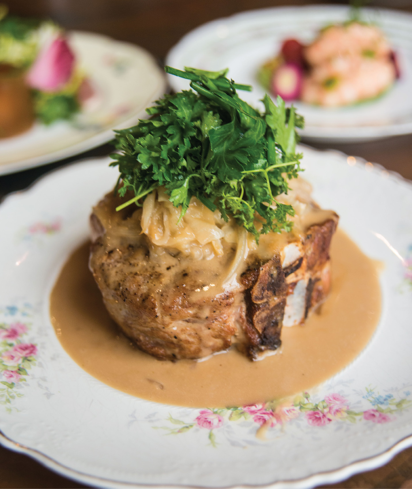 Some Chops: Bathed in a classic French mustard sauce, the grilled pork porterhouse gets dressed with melted onions and a leafy herb salad.