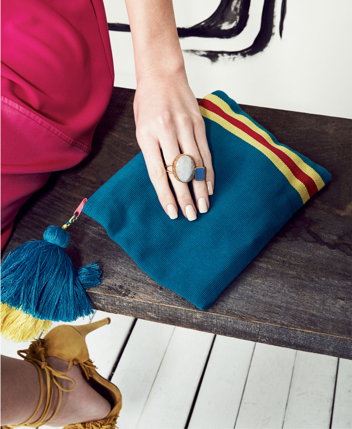 Pais Textil turquoise zip clutch with yellow and pink stripe, $40 at ibu; and Heather Tiller 18K gold vermeil and large moonstone ring, $155, and blue chalcedony ring, $80, both at Filigree