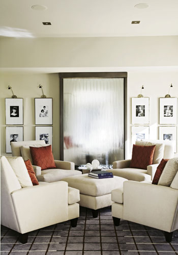 In Its Element: The focal point of the reading room is a floor-to-ceiling waterfall framed by a collection of black-and-white portraits of the couple and their triplets.