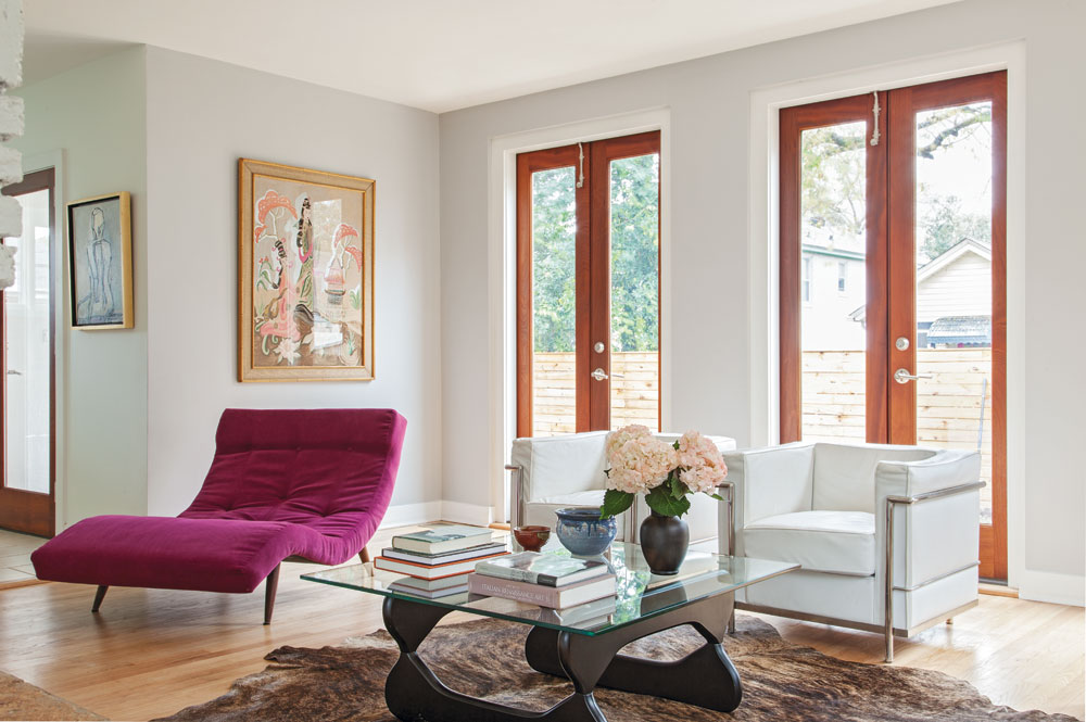 BY DESIGN: In the living room, a few strategic design tweaks made a big impact. A row of windows were swapped out for sapele French doors, strengthening the relationship between the living area and the outdoors. A chaise lounge was recovered in an eye-catching purple hue to suit the home's new vibe.
