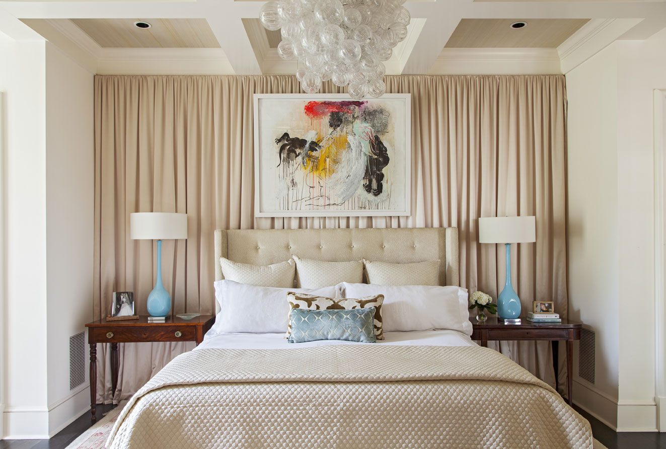 Above the bed, a sculptural chandelier hangs near a colorful abstract piece by local artist Tim Hussey.
