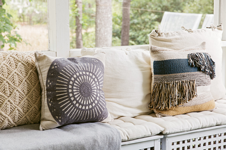 Mix & Match: Therese outfitted bench seating on the screened porch with cushions and woven pillows in soft blue and cream colors.