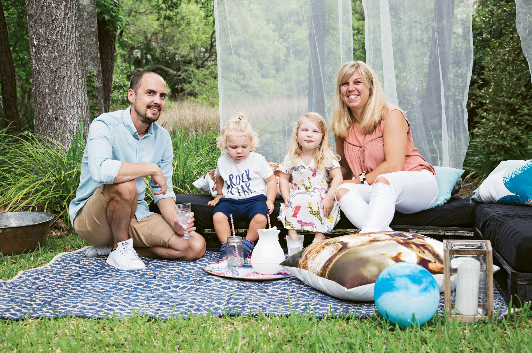 FAMILY TIME: Jacob and Therese Lenberg picnic with their children in their Hobcaw Creek backyard. The Swedish couple's abode is chock-full of Scandinavian style, beginning with the entryway (left), where one clock is set to local time and another displays the hour in their hometown of Gothenburg.
