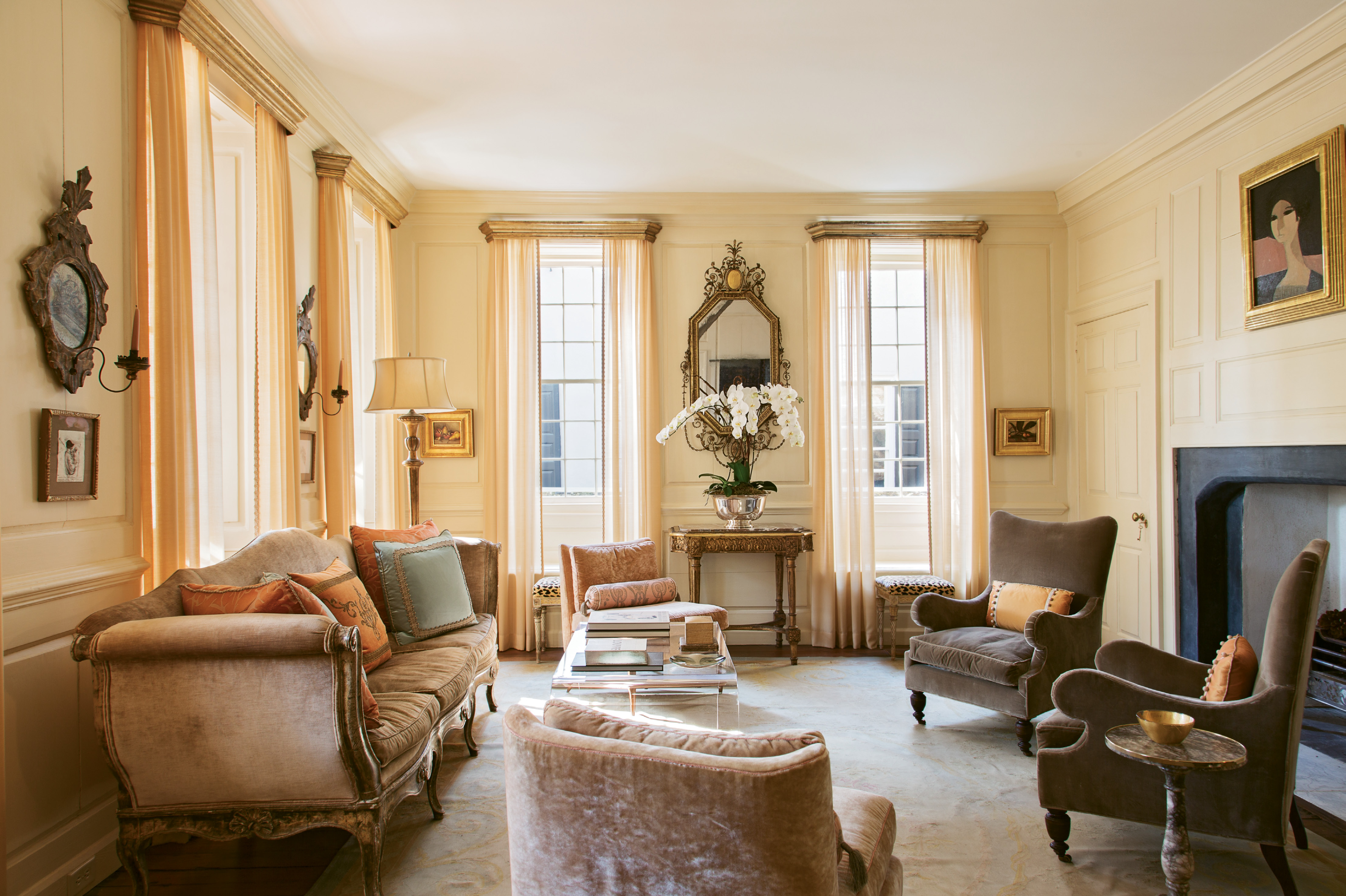 "A 1968 portrait by French painter André Minaux sets the tone for the first-floor drawing room. ""She has that little bit of pink,"" says Ann. ""We put her right over the classical Georgian fireplace and suddenly the room got very feminine."" Sketches by Ben Long and two still lifes by Jill Hooper round out the room's luxe vibe."