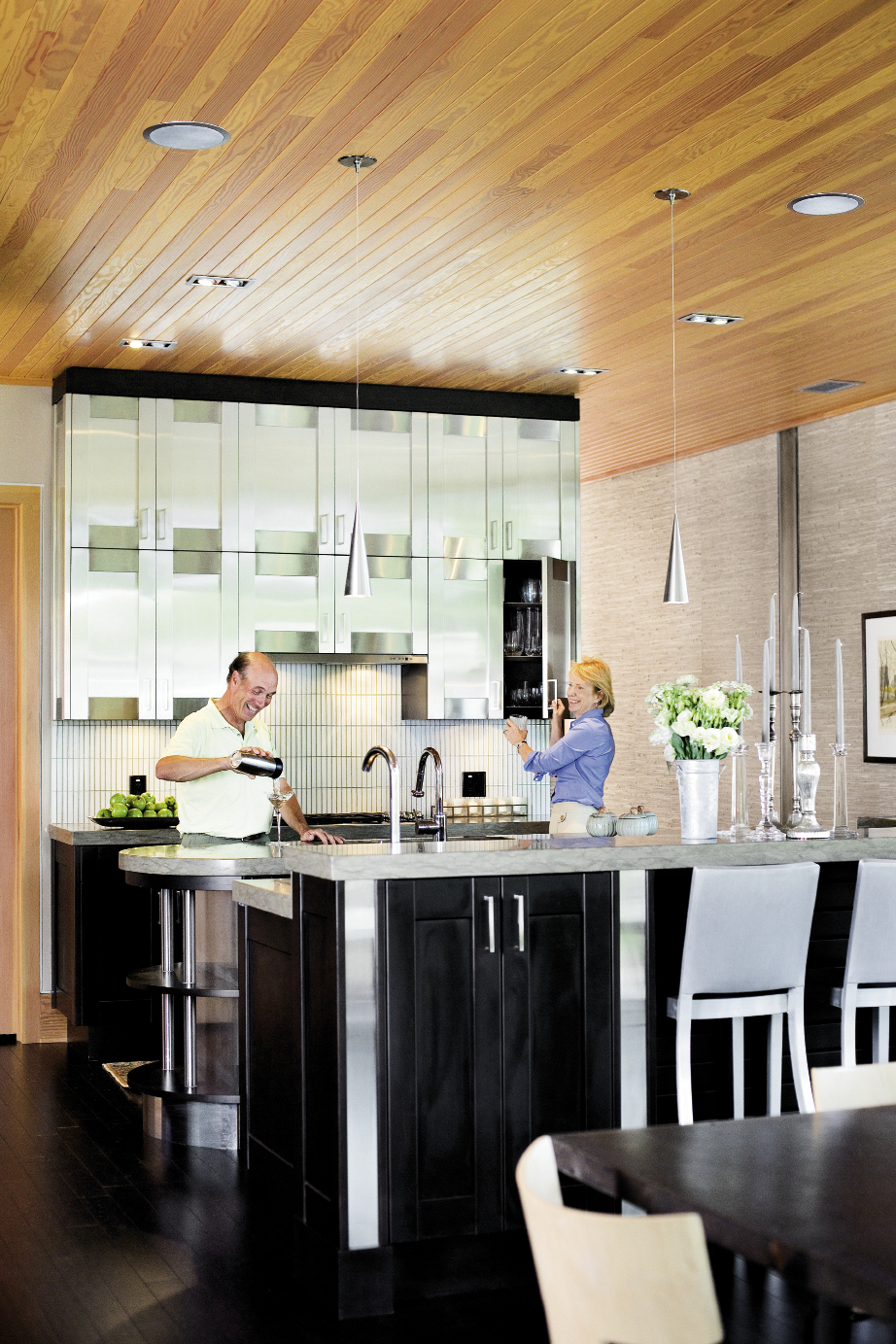 the pair in their open kitchen, anchored by stainless steel upper cabinetry.