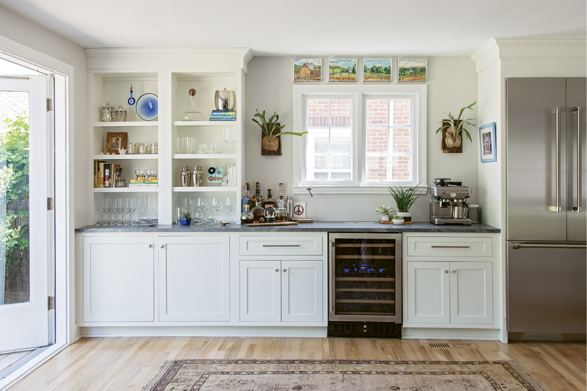 The kitchen flows into an open, airy entertaining space, which Rachel left free of furniture to allow for yoga sessions and late-night dance parties. There, antler-like staghorn ferns from Hyams Garden Center flank the window.