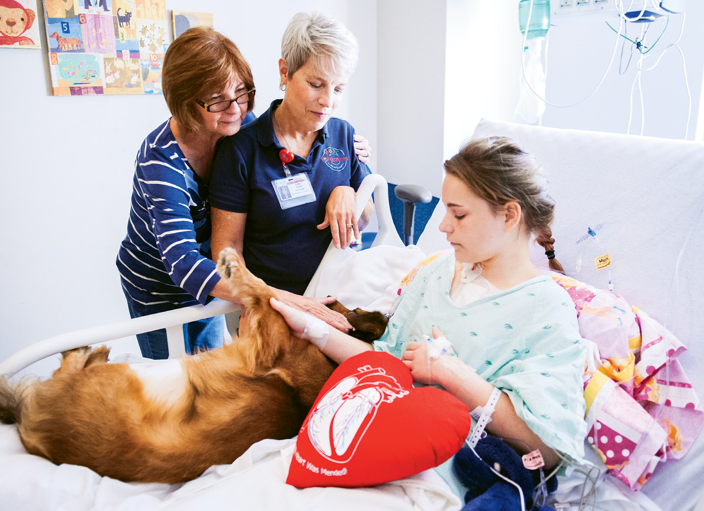 Kathy Sykes (standing at right) brings pooches Bristol—shown with young Sydney and a family member—and Maddie to MUSC twice a week.