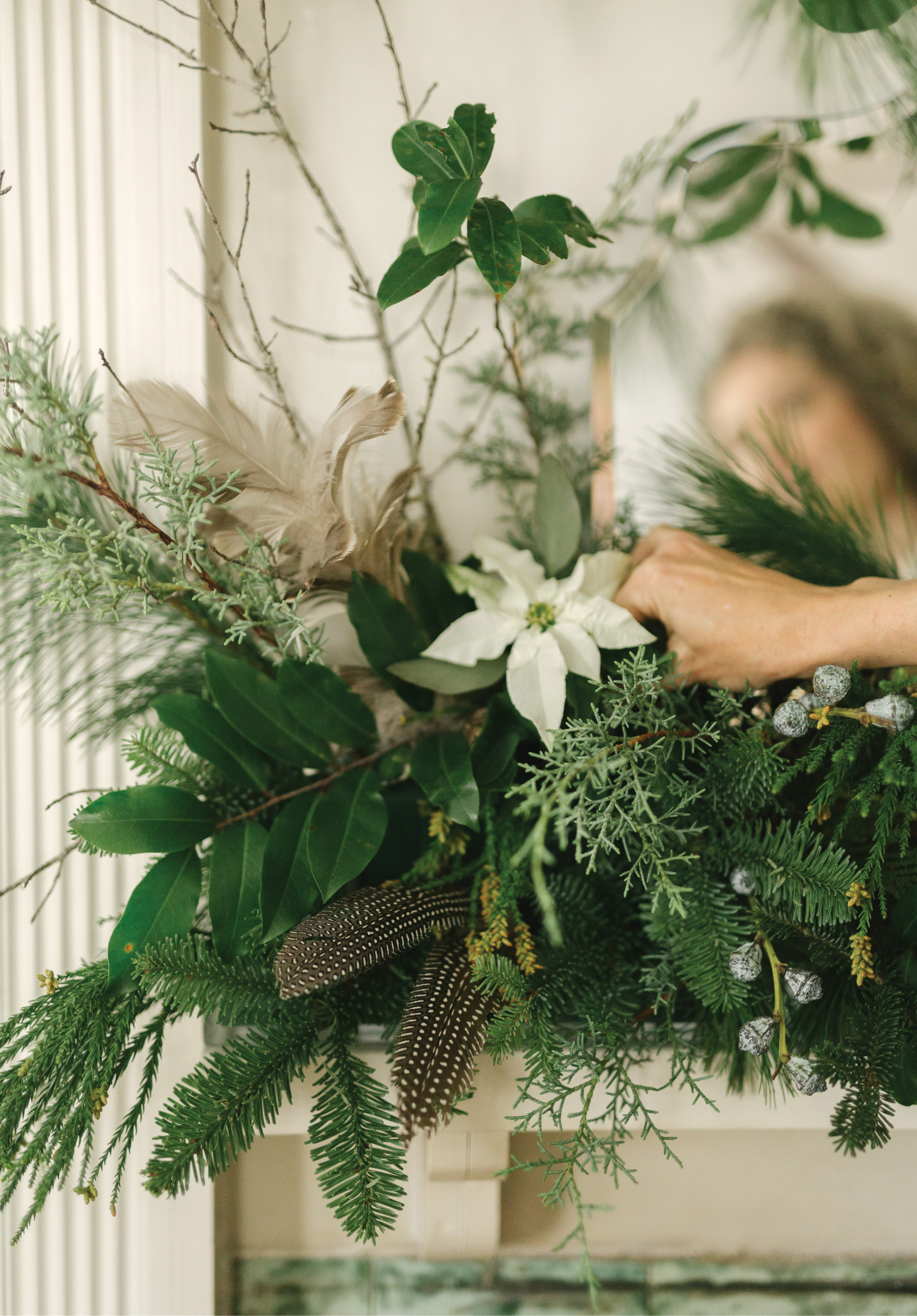 For her dramatic mantelpiece, she fills narrow Lucite trays with floral foam, then a mix of greens plus branches covered in lichen, silver-hued Cecropia leaves, and guinea hen feathers for tons of texture and a woodsy feel.