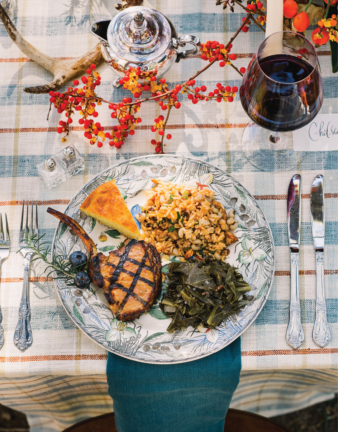 Each household sits at their own table with the sides they made served family-style. The host wore a mask and gloves to grill pork chops for all.