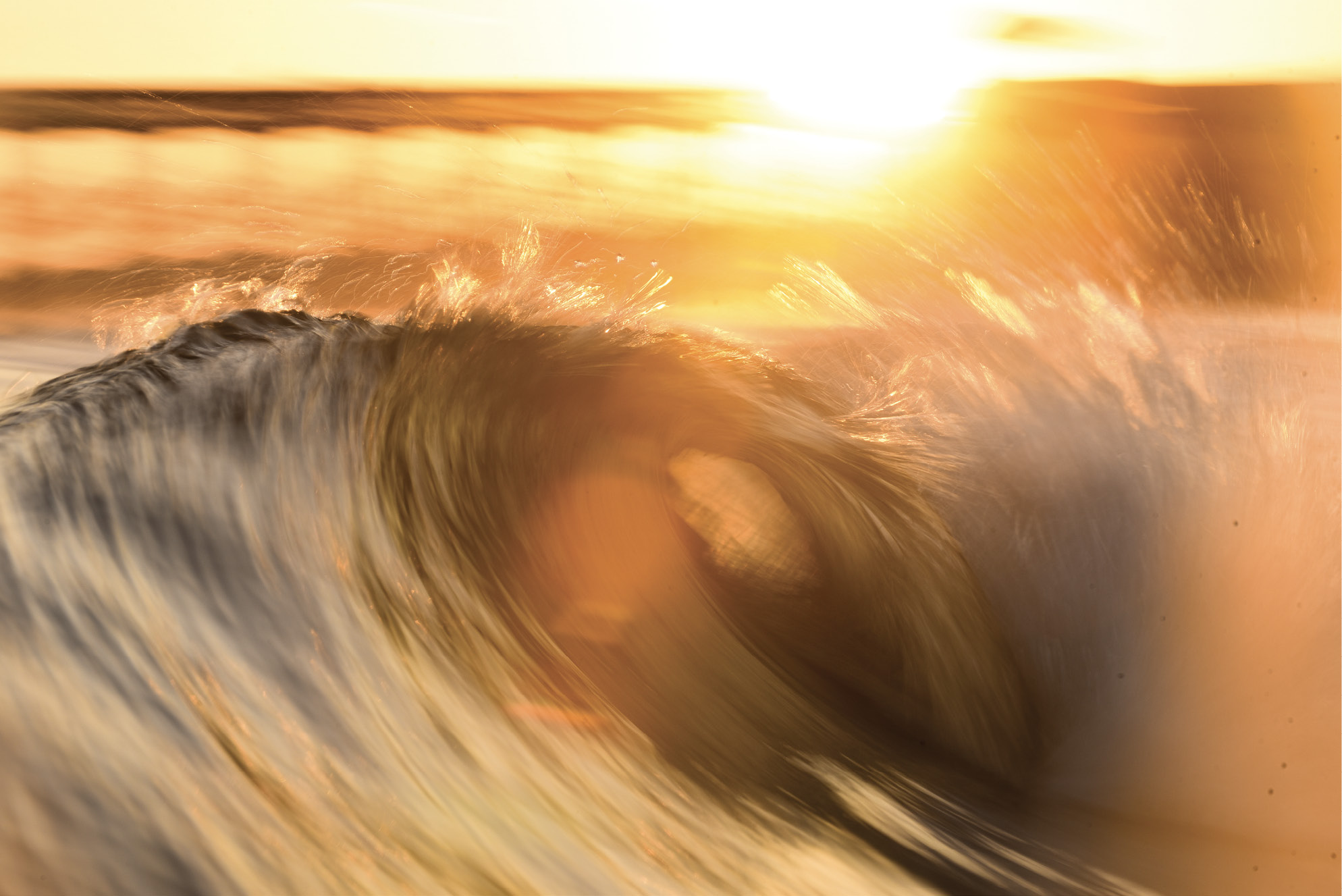 A setting sun and a slower shutter speed capture the movement of the waves.