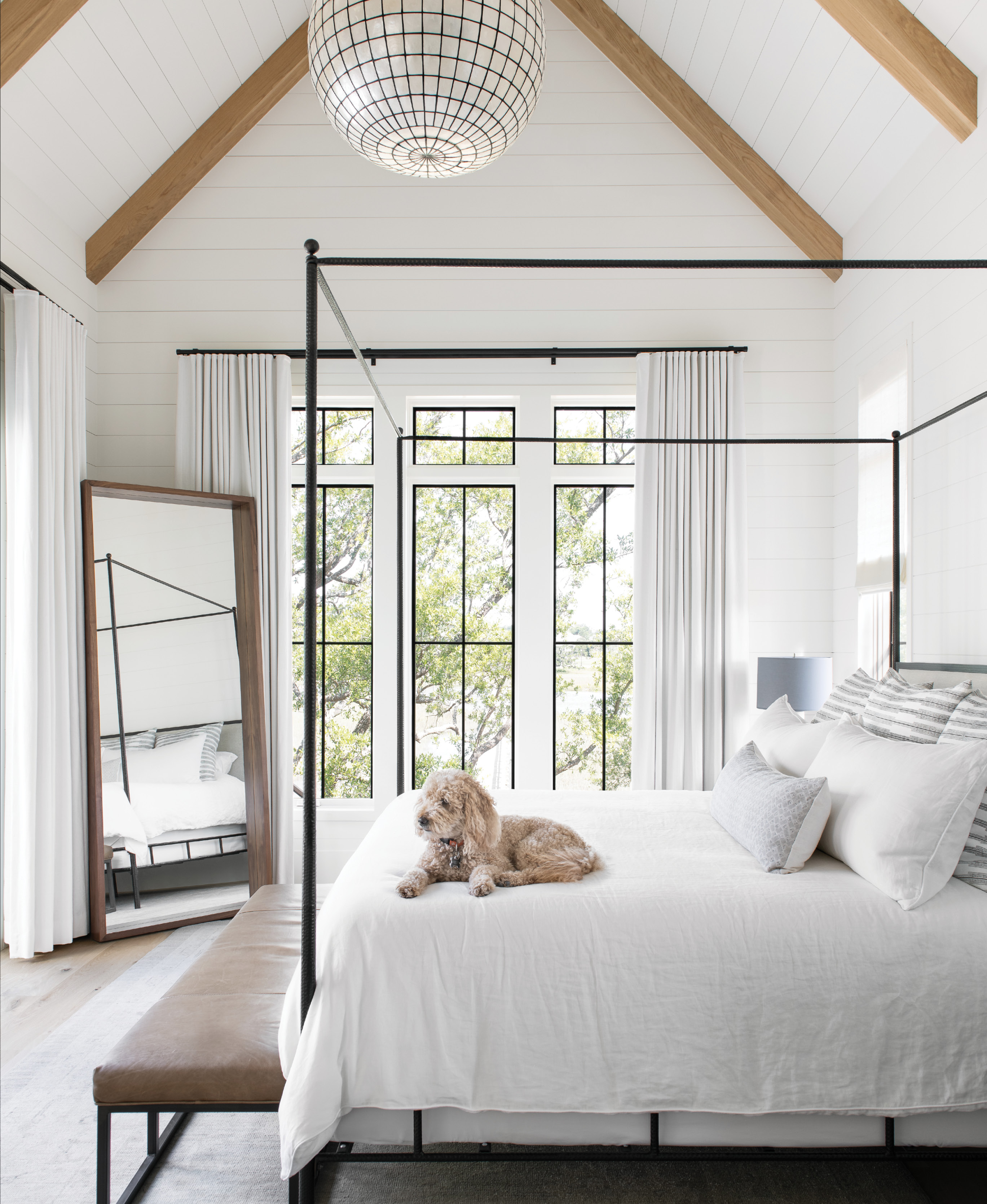 """Simply Luxe: The paired-down master suite feels glamorous yet comfortable. Tying into the black steel of the windows, the iron-framed """"Marco Bed"""" by Oly Studio is softened by plush Peacock Alley bedding and a worn leather bench atop a vintage Oushak rug. A Restoration Hardware chandelier and Room & Board mirror complete the space."""