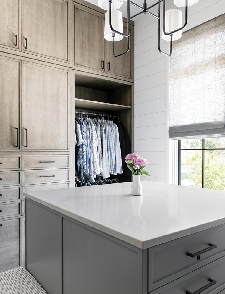 Distinctive Design's custom cabinets and island in the large walk-in closet keep clutter at bay.