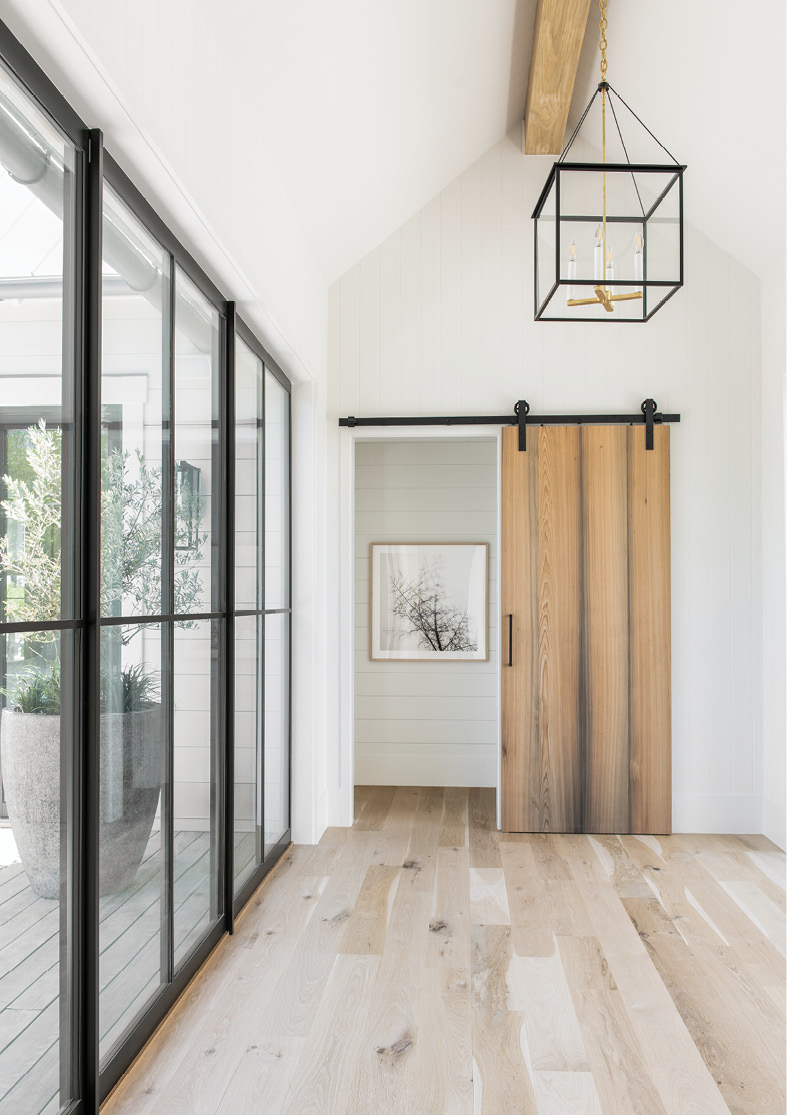 Feature & Function: Designed to draw the eye to the landscape beyond its floor-to-ceiling windows, the entryway's white oak flooring, cypress barn door, and wooden beam are accented by steel and glass, including an Urban Electric light fixture and custom door hardware.